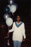 A picture of an unidentified Black woman smiling near a staircase, 1990