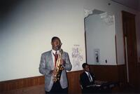 A picture of a two unidentified Black men performing at an event, 1990