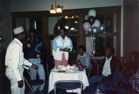 A picture of a group of unidentified Black men gathered around a table at an event, 1990