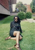 An unidentified Black woman sitting on the lawn in front the Christensen Center, 1996