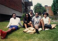 A group of unidentified Black people and an unidentified woman smiling in front the Christensen Center, 1992