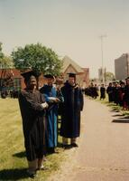 An unidentified Black man standing next to two unidentified men at a graduation commencement, 1996