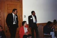 Two unidentified Black men standing next to an unidentified woman and others, 1992