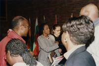 An unidentified Black woman meeting a group of unidentified Black people and others, 1996