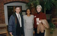 An unidentified black woman poses with two unidentified people, 1996