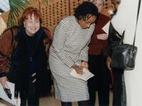 An unidentified Black woman signing a program next to others, 1996