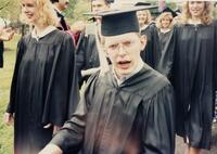 An unidentified man poses in front of others smiling before a graduation commencement, 1992