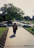 An unidentified Black woman walking on Augsburg College's campus, 1996