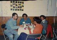 Three unidentified Black women and an unidentified Black man sitting at a table together, 1993