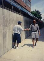 Two unidentified Black men shake hands on a pathway, 1993