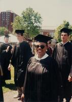 An unidentified Black woman smiling for a picture at a graduation ceremony, 1995
