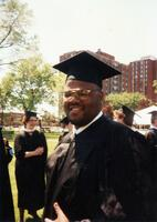 An unidentified Black man smiling for a picture at a graduation ceremony, 1995