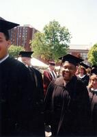 An unidentified Black student smiling while walking to commencement at Augsburg College, 1995