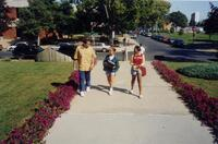 An unidentified Black woman walking with two unidentified people, 1998