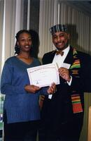 "Brother Joe Young posing for a photograph with Roshonda White holding a certificate that reads ""Pan-Afrikan Celebration,"" circa 1997"