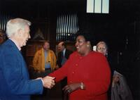 An unidentified Black person shaking hands with an unidentified person, circa 1997