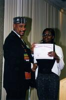 "Brother Joe Young posing for a photograph with an unidentified Black person who is holding a certificate that reads ""Pan-Afrikan Celebration,"" circa 1997"