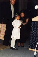 A Black child speaking into a microphone as an unidentified Black person helps her, March 1997