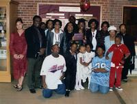A group of Black people pose with a Black graduate, 2004