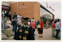 A Black graduate posing outside Si Melby Hall, 1995