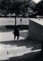 An unidentified Black person walking up stairs at Old Main, circa 1990