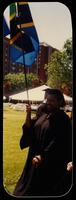 A Black graduate holding a flag by Murphy Square, circa 1995