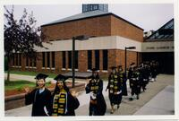 Black graduates and other graduates walking out of the Foss Center, circa 1995