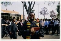 A Black graduate smiles during commencement, circa 1995