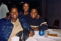 A Black person posing for a picture, smiling with their family, 2004