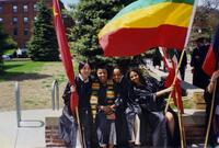Graduates taking a photograph together, waving flags, 2004