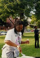 An unidentified Black person cooks food in Murphy Square, 1999