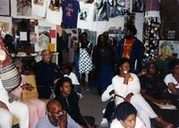 A group of Black people listening to a speaker, circa 1995