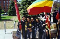 Four unidentified graduates holding flags smiling together, 2004