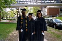 Three unidentified people dressed in a cap and gown take a picture together, 2004