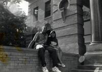 Two unidentified people sitting on a wall in front of Old Main Hall, 2004