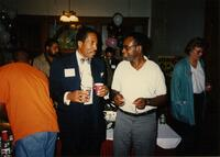Two unidentified Black men speaking at a Pan-Afrikan event, 1990