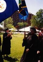 An unidentified Black woman holding a flag during a graduation commencement, circa 1995