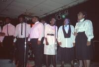 A group of Black people performing music on stage, circa 1990