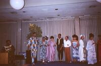 An unidentified Black person speaking into a microphone while a group of Black people stand on stage, circa 1990