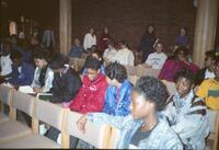 Black people and others sitting in the audience in the Hoversten Chapel, circa 1990