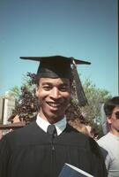 A graduating Black senior smiling for a photograph, circa 1990