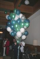 An unidentified Black person holding balloons in Old Main, circa 1990
