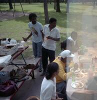A group of unidentified Black people eating at Murphy Square, circa 1990
