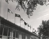 Si Melby Hall, flags on west facade, facing southeast, circa 1962.